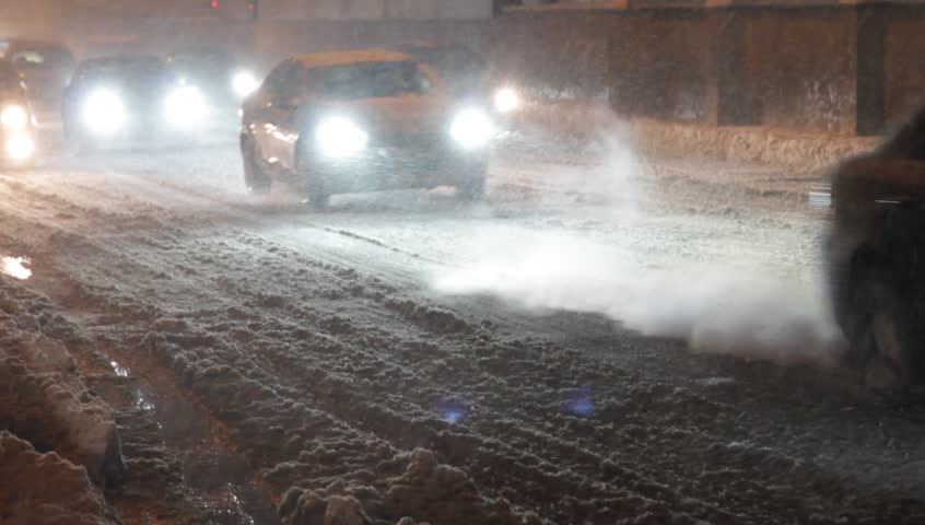 Cars move along the evening snow-covered road with the lights on during heavy wet snow   Shutterstock HD Video #34084810