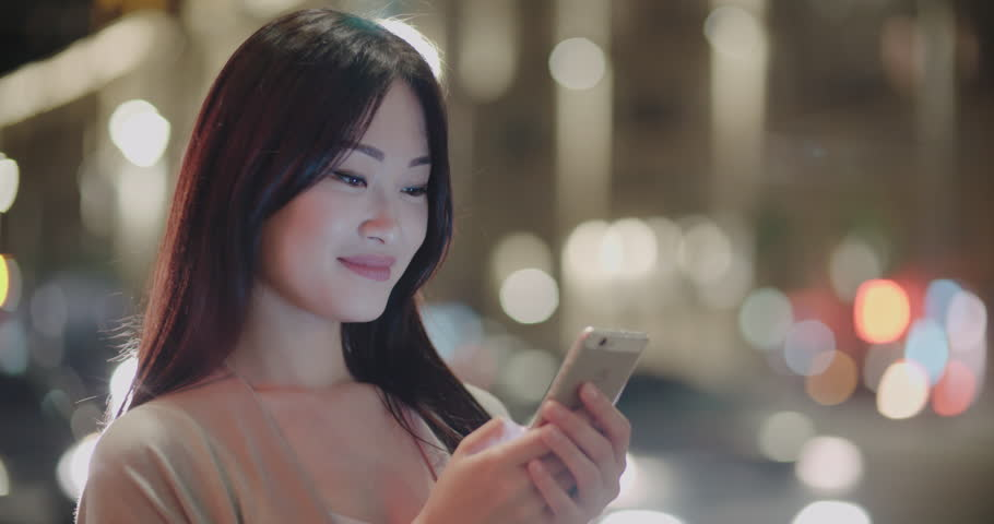 beautiful Asian girl in the night metropolis, uses a smartphone for communication, writes the message with a smile, Steadicam shot Royalty-Free Stock Footage #34086634