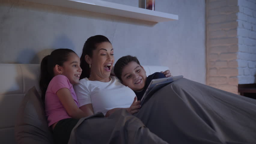 A mother and her children in bed enjoy a streaming movie in their tablet during a weekend night. A single caucasian woman and her kids having fun spending quality time together.  Royalty-Free Stock Footage #34086679