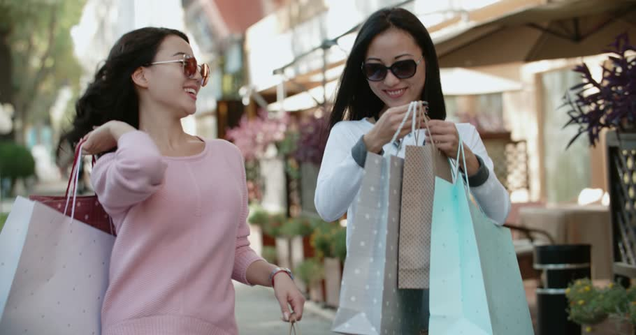 two beautiful Asian girls have fun walking down the street with their purchases after shopping , Steadicam shot