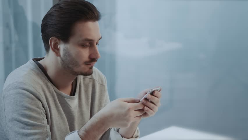 Portrait of young businessman talk on cellphone while stand by his office window in modern interior of skyscraper building, male entrepreneur having mobile phone conversation after important briefing #34096864