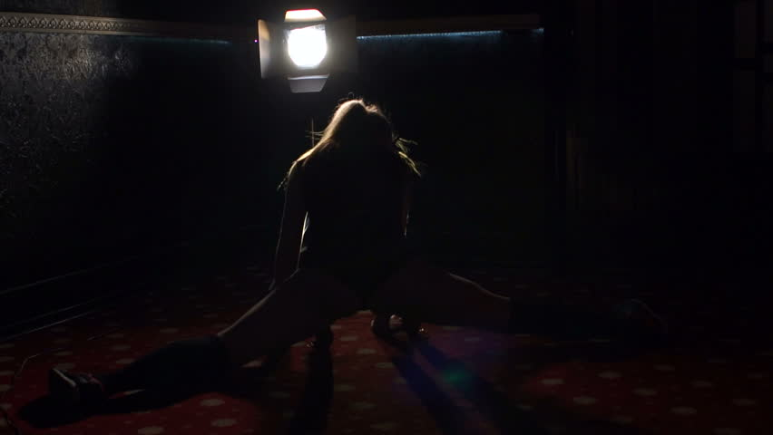 Close-up silhouette of a sexy girl shaking booty in the dark with the spotlight. | Shutterstock HD Video #34106566