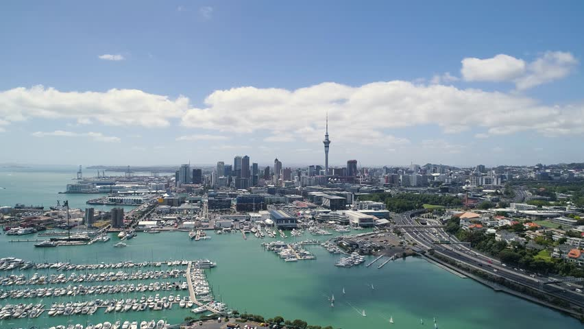 Aerial view of skytower city skyline and marina, flying toward sea, highway traffic, boats traffic.