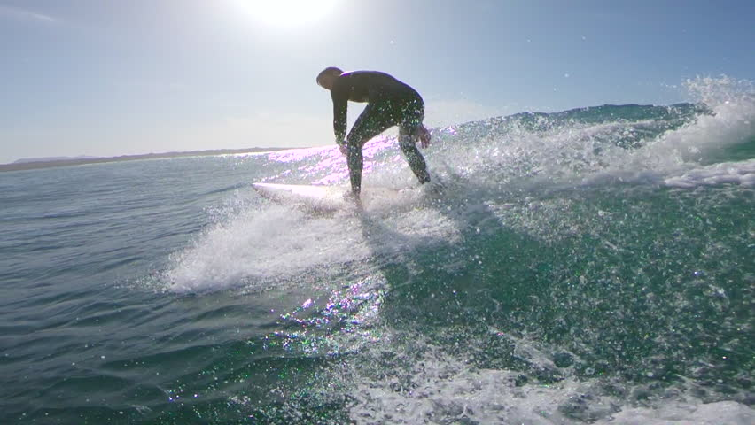 SLOW MOTION, LENS FLARE: Surfboarder riding a small wave on a bright sunny day. Exciting slow motion of male surfer riding wave in the Canary Islands. Intense sunlight reflecting off clear blue ocean   Shutterstock HD Video #34135090