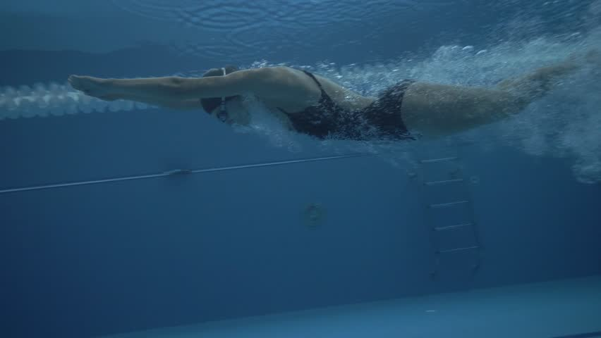 Woman swimmer jump on deep water in floating pool at start slow motion. Close up woman dive in transparentwater on swimming pool under water view 60 fps