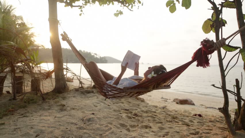 Young woman reading a book while lying down on a hammock surrounded by nature. Woman on hammock reading a book by the beach at sunset, female relaxing on hammock by the beach