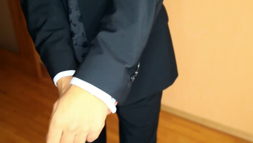 Closeup well-dressed groom puts on black suit jacket and removes lint from sleeves dressing up for wedding | Shutterstock HD Video #34143181