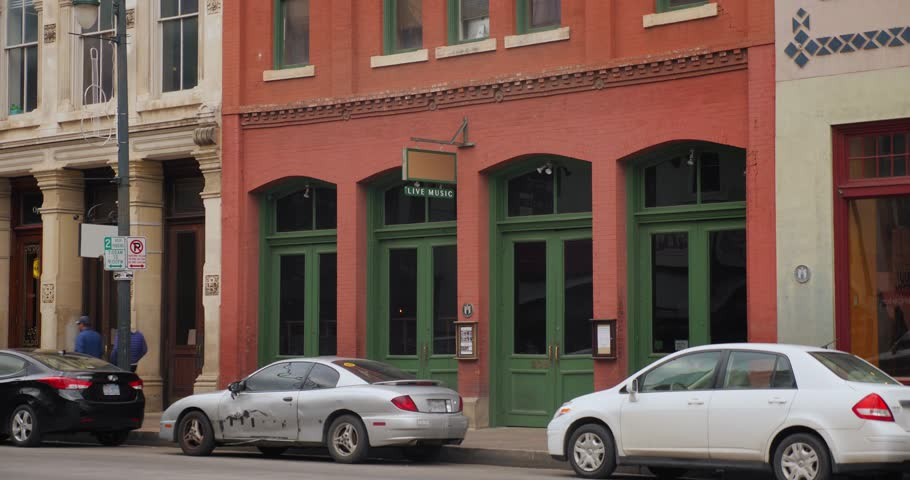 A daytime establishing shot of bars and restaurants on E 6th Street in the historic tourist district of Austin, Texas. Day night matching available.