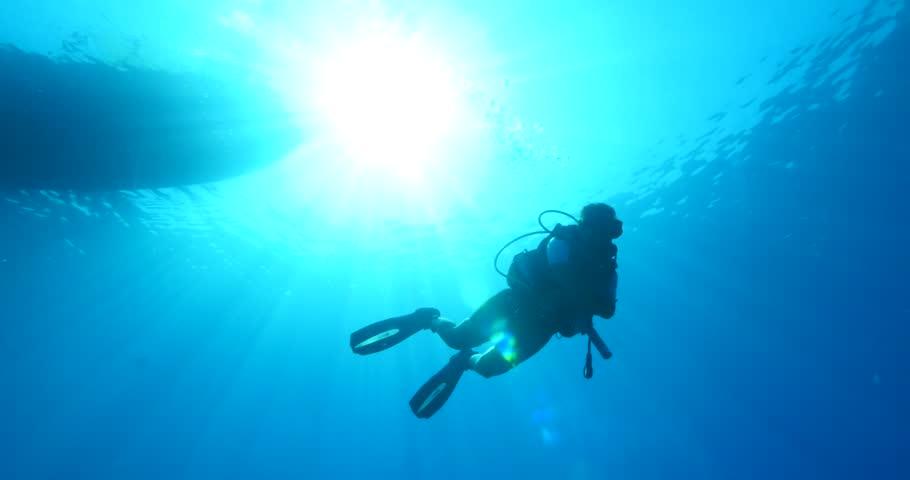 diver under sun beams and light underwater sun shine scuba diver silhouette starting dive