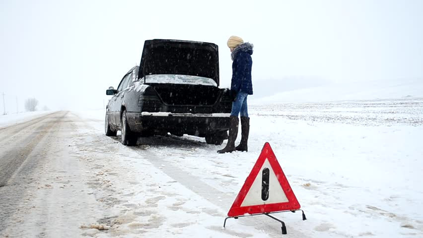 Car broke, need to put the spare tire, woman talking on a cell phone, calls for help, an emergency on the road in winter, dangerous winter road covered with snow