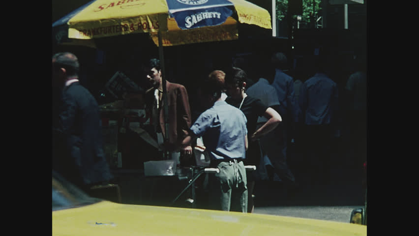 NEW YORK, 1971, Hot Dog cart with man selling hot dog on street, cabs and taxis pass