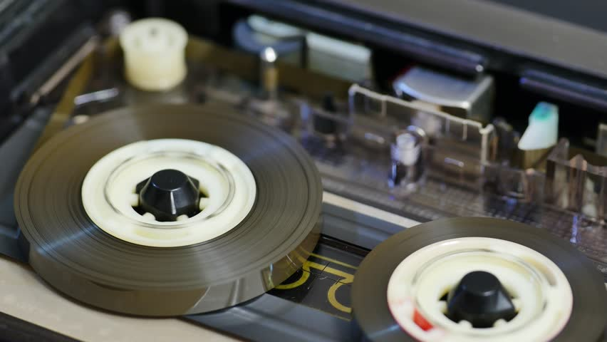Cassette tape assembly of audio recorder spinning slowly. Tape reel starts the recording or playback. Shallow Depth of Field, Close Up, Angled View