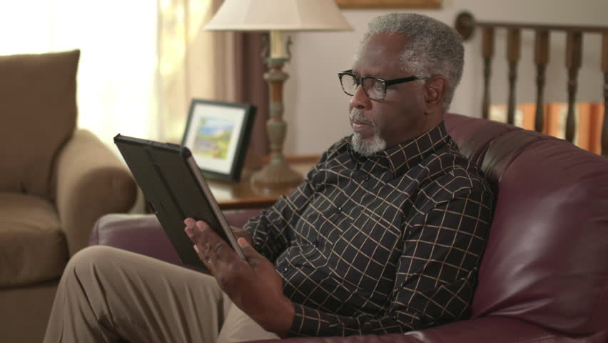 Elderly African American retiree online using a tablet computer, reading. Authentic at home lifestyle shot. Slow motion (48fps) Prores file.