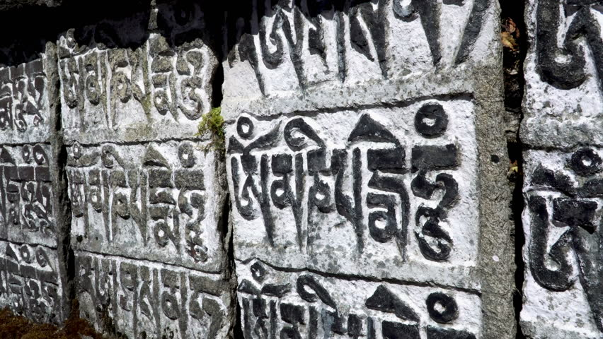 Traditional prayer stone with a Buddhist mantra: om mani padme hum. Translation: Pearl in a lotus flower! | Shutterstock HD Video #34207510