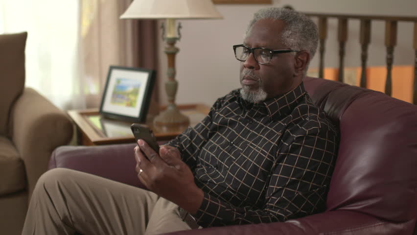 Elderly African American retiree using a smartphone to browse online and read. Authentic at home lifestyle shot. Prores file.