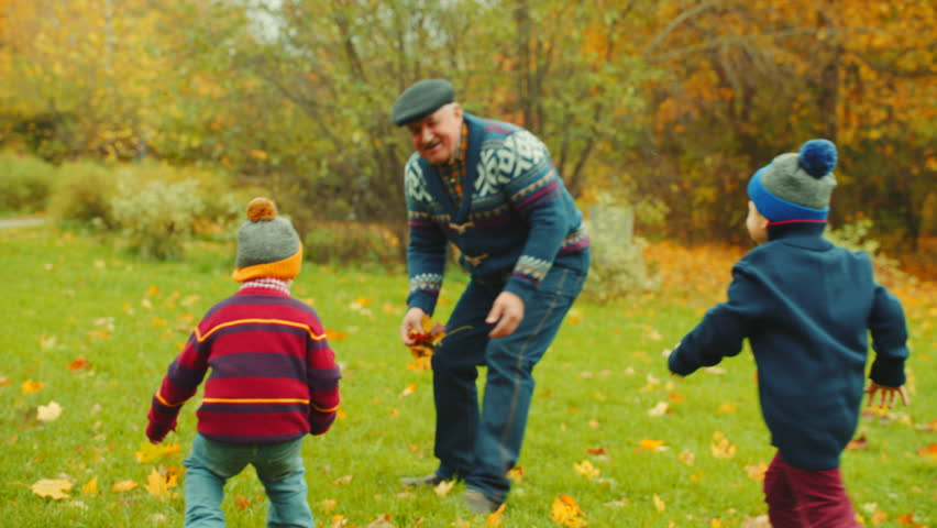 Grandfather is playing catch-up with his grandchildren in the autumn park