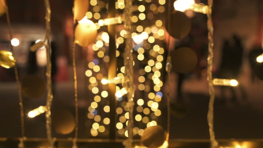 Blur silhouettes, crowd of people walking on decorated street during holiday season like Christmas and New year, light decoration bokeh as abstract holiday season background | Shutterstock HD Video #34215952