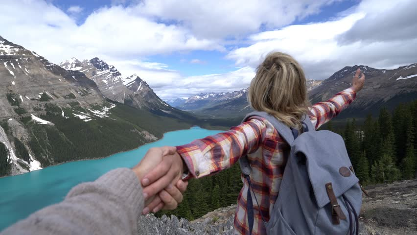 Follow me to- Young woman leading man to Peyto lake in Banff national park, Canada. People travel sharing moment concept. | Shutterstock HD Video #34225414