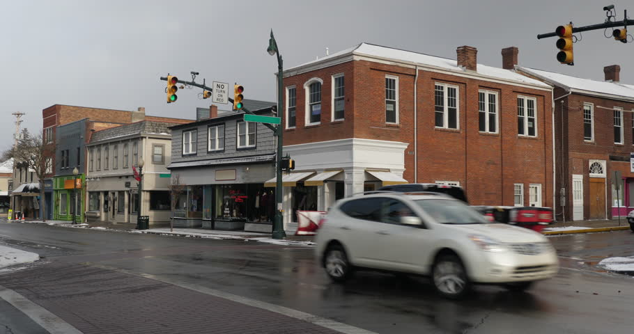 A daytime winter establishing shot of businesses on a typical Main Street in America decorated for Christmas. Snow plow truck passes by. Pittsburgh suburb. Summer and night version available.