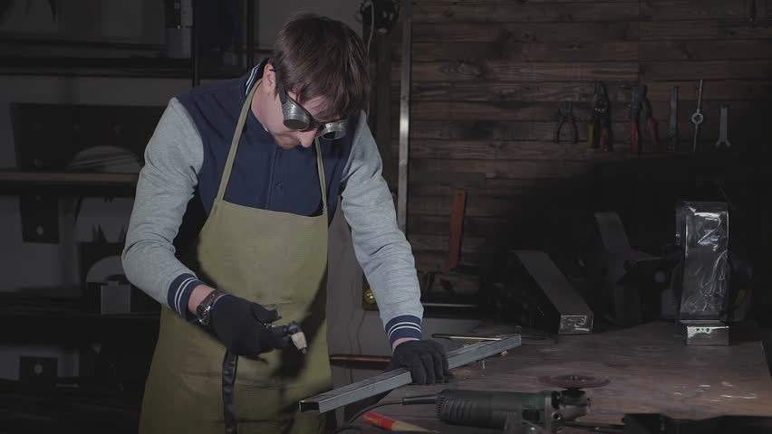 Blacksmith cuts iron details via plasma cutter at his workshop. Metalwork with sparks in slow motion. #34247821