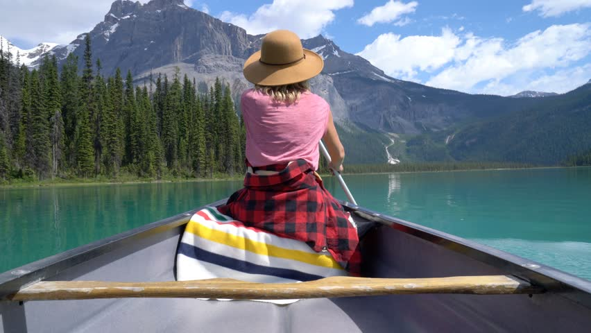 Young woman canoeing on stunning pristine emerald lake. Woman paddling canoe on turquoise lake in the middle of the Canadian rockies. Stunning mountian lake scenery  | Shutterstock HD Video #34250323
