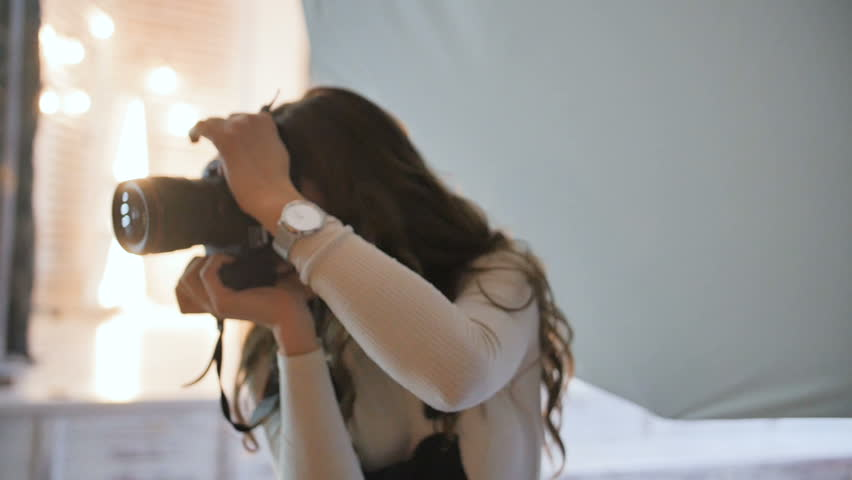 Young beautiful photographer with the professional camera. Shooting, laughing and having fun. Smile