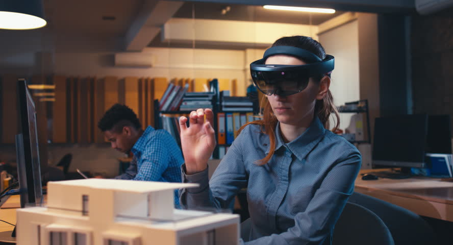 Caucasian female professional architect using augmented reality AR hololens headset to work on a house project. 4K UHD RAW edited footage #34257037