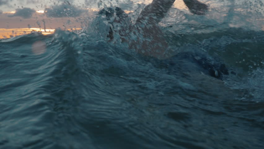 slow motion of professional swimmer swimming crawl outdoor on sunset, front view Royalty-Free Stock Footage #34262419