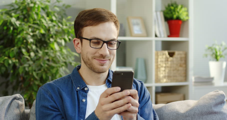 Portrait shot of the good looking smiled man in glasses holding a black smartphone in his hands and taping on it while having a chat in the cozy living rom. Inside. Close up | Shutterstock HD Video #34266487