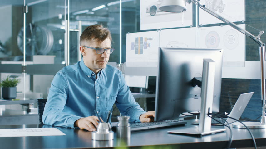 Experienced Industrial Engineer Working on Personal Computer in the Stylish, Modern, Glass Office. Shot on RED EPIC-W 8K Helium Cinema Camera.