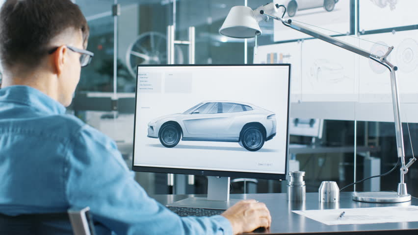 Automotive Engineer Works on the Personal Computer, He Perfects New Car Model Prototype Sketch. He Works in the Bright and Modern Office. Shot on RED EPIC-W 8K Helium Cinema Camera.