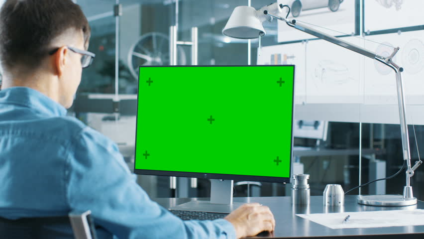 Automotive Engineer Working on a Personal Computer With Isolated Mock-up Green Screen on it. He Works in the Bright and Modern Office with Car Sketches on the Walls. Shot on RED EPIC-W 8K Helium Cinem