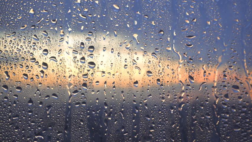 Drops of rain on a window pane, buildings in background | Shutterstock HD Video #34272091