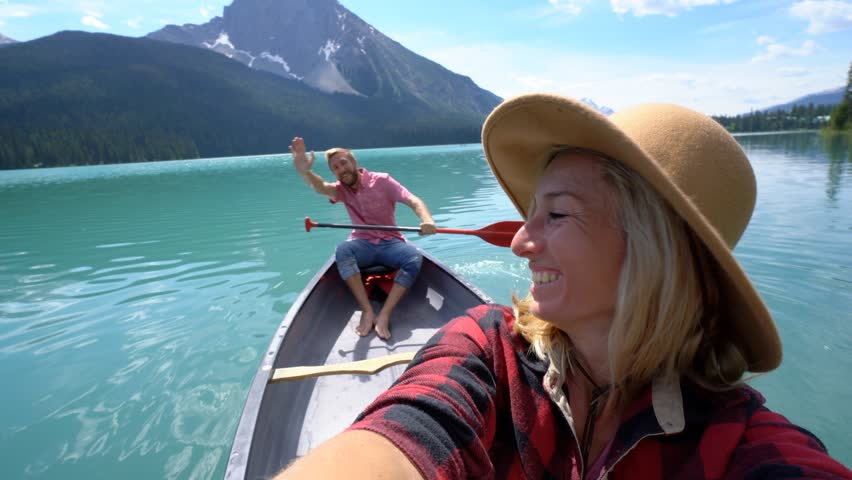 Young couple canoeing on a beautiful lake in Canada, taking selfies. Selfie portrait of couple canoeing on Emerald lake, Canada