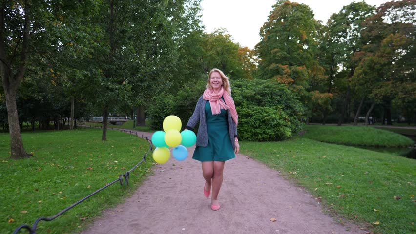 Positive young woman walk and happily skip at evening park. Dolly slow motion shot. Nice path and green environment. Girl hold balloons in hand, smile and look straight to camera | Shutterstock HD Video #34317502
