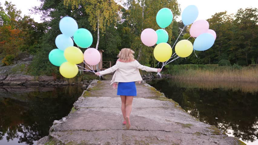 Young woman happily run away by old pier in high spirits, holding nice flying balloons in both hands. Slow motion shot, follow camera move behind. Concrete walkway lead to green park, autumn season | Shutterstock HD Video #34317505