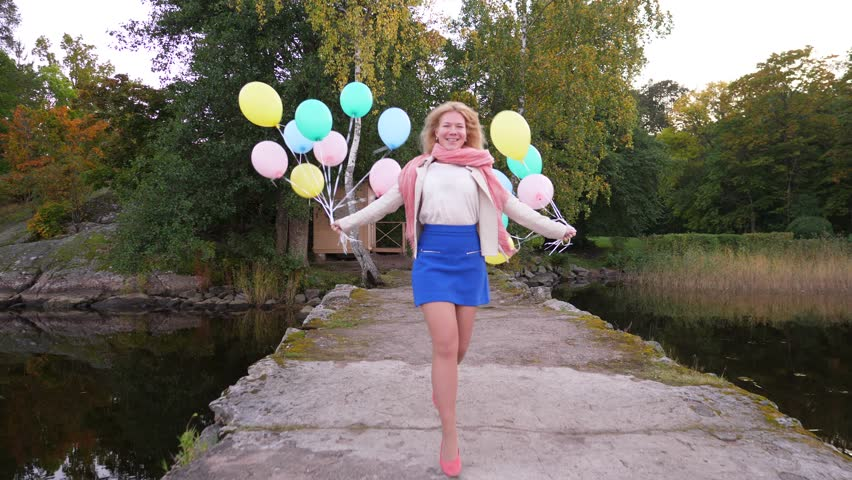 Cheerful young woman happily run towards camera along old pier with flying balloons in hands, evening park on land. Slow motion shot, happiness and positive mood concept | Shutterstock HD Video #34317526