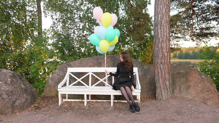 Young adorable woman in black dress sit on bench, hold light balloons in hand. Girl look beside, then quickly turn head to other side. Nice calm sitting area at large park, soft evening time | Shutterstock HD Video #34317541