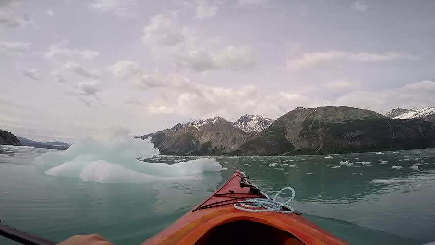 A lone Kayak approaching an iceberg in Glacier Bay National Park, Alaska.  #34328032