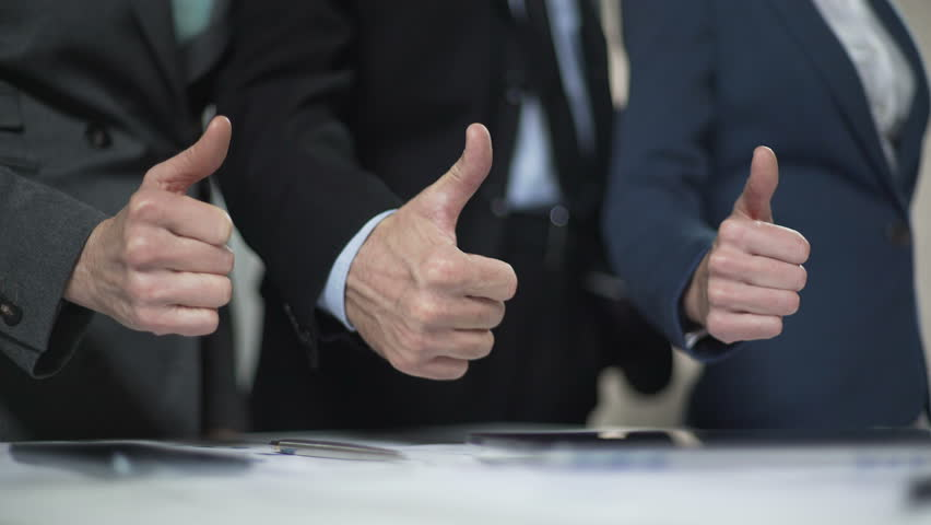 Coworkers showing thumbs up, campaign office promise candidate election victory