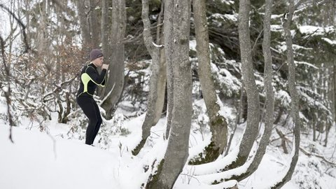 Young man shadow boxing in a forrest in Austria in the winter