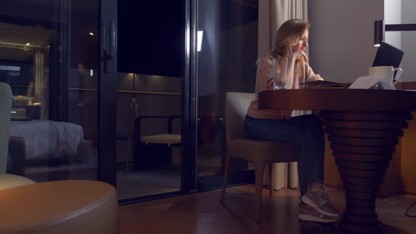 Woman working on a laptop at a table at night in a hotel room. 4k. she falls asleep in the workplace, yawns. | Shutterstock HD Video #34365502