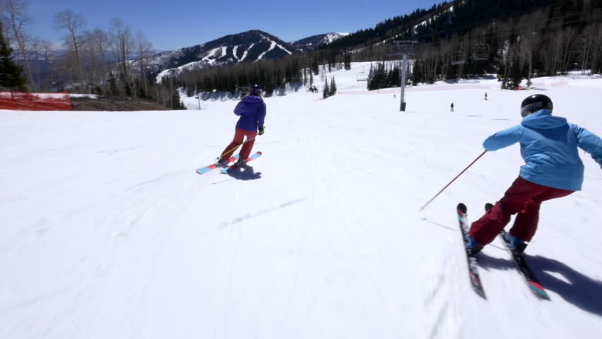 Cameraman skis alongside with two female expert skiers on a sunny day at the Canyons Village Park City, Utah.