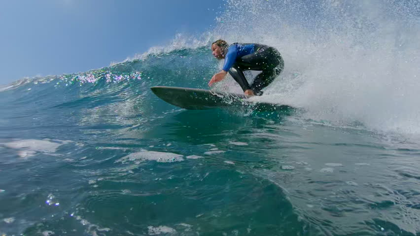SLOW MOTION, LOW ANGLE, UNDERWATER: Young man surfing a big crashing ocean wave in sunny nature. Surfer carving awesome wave on his cool surfboard. Fit surfer guy riding waves in popular surf spot.