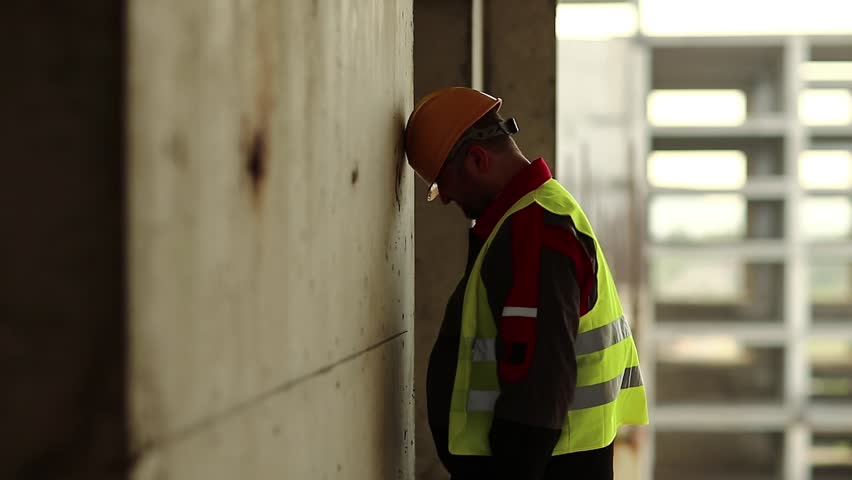 Workman knocks his head against the wall. Stressed worker in hard hat stands on construction site and knocks his head against the concrete wall, self-condemnation and self-torture