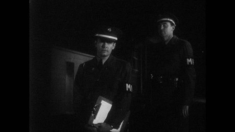 1950s: UNITED STATES: guards work at gate. Guard opens package. Man looks anxious