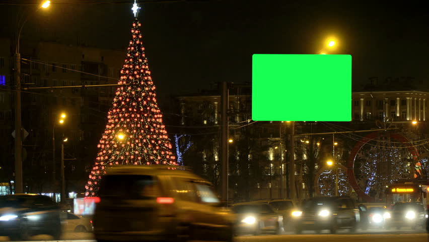 Copy space Billboard green screen, Christmas tree glows brightly in night city winter snow-covered road amid traffic jam passing cars, concept Christmas eve, new year, snow, blowing Blizzard, cars