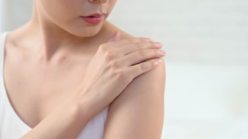 young female touching her perfect hairless smooth soft and silky shoulder arm skin.