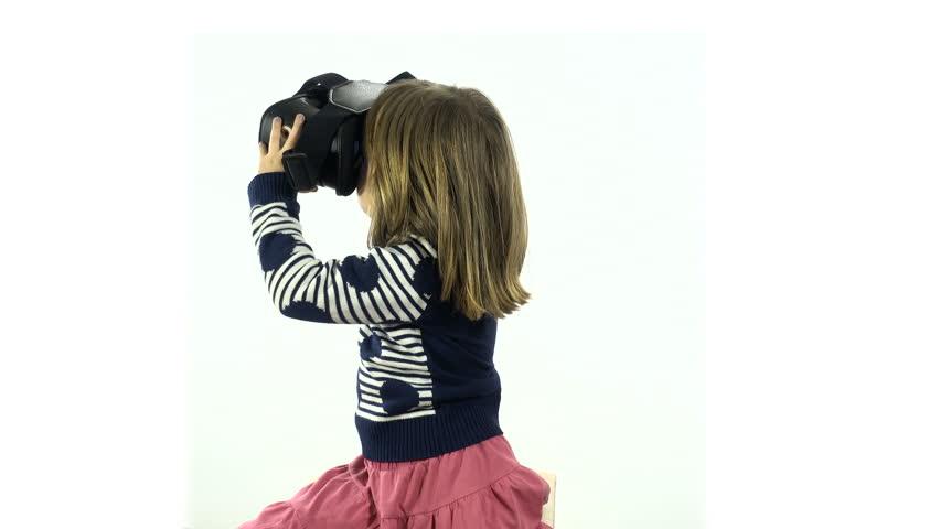 Studio, white background. European or american child wathing movei in vr virtual reality glasses.