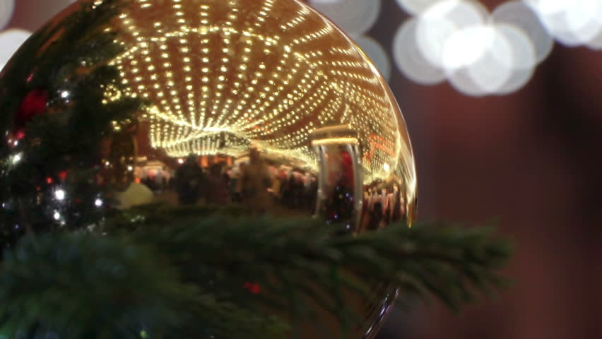 Christmas shiny ball on Christmas tree at fair with carousel, crowd of people reflected in Orb as mirror, Concept christmas family shopping, people walking at New Year's eve close up | Shutterstock HD Video #34427080